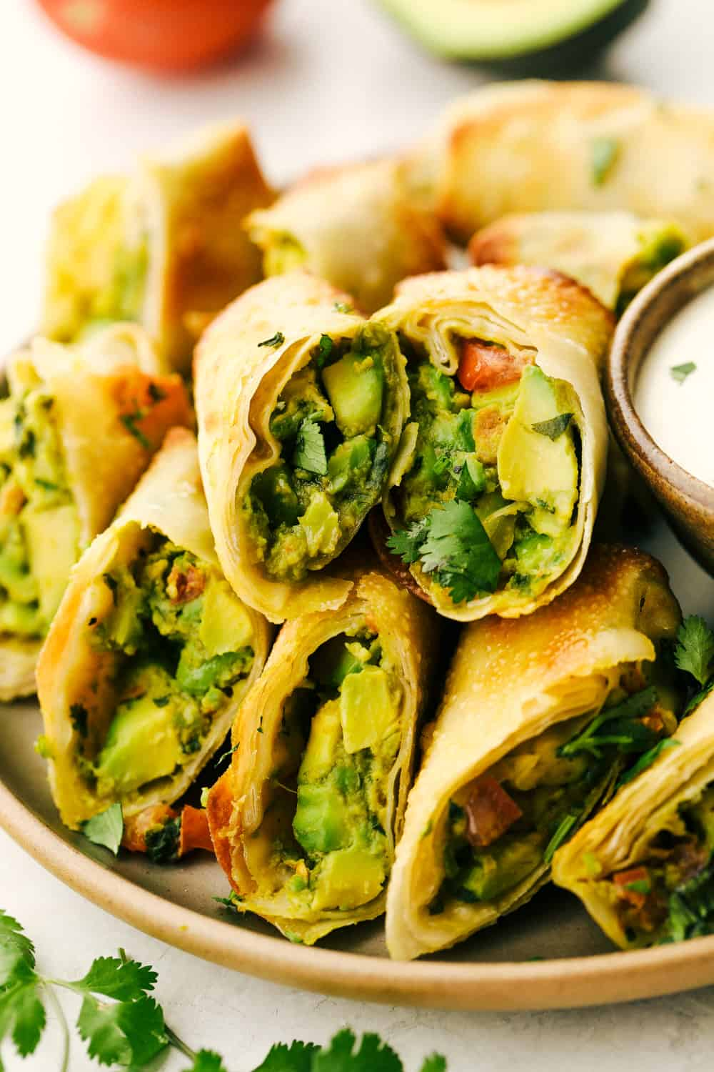 Avocado egg rolls split and layered on a plate.