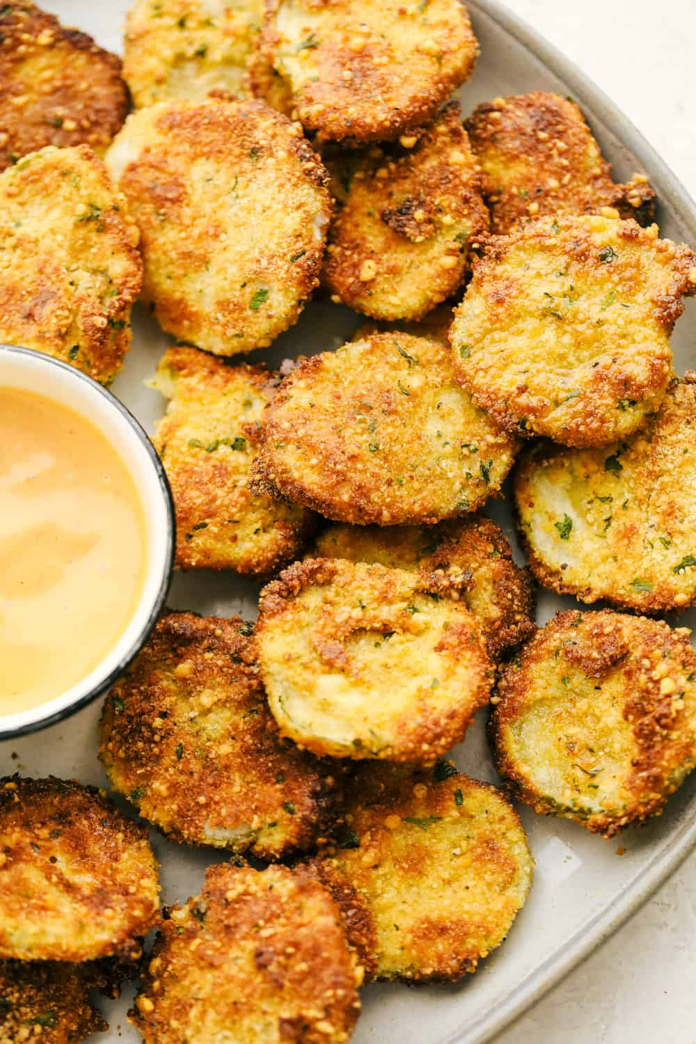 Air Fryer fried pickles with sauce on a platter.