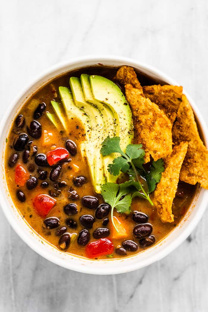 Black bean soup in a white bowl with avocado on top.