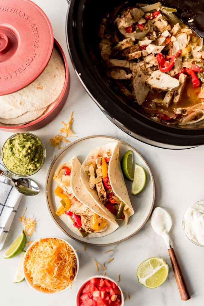 Chicken fajitas with toppings next to a slow cooker.