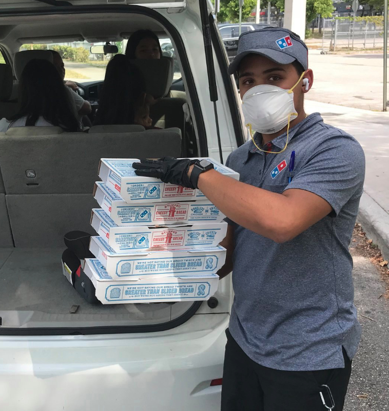 Domino's pizza delivery man wearing mask