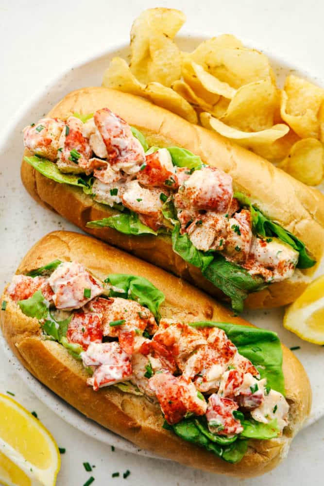 Finished lobster rolls on a white serving plate with chips.