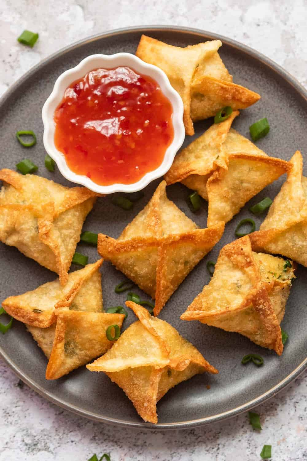 Crab rangoon served on a grey plate with sweet chilli sauce on the side