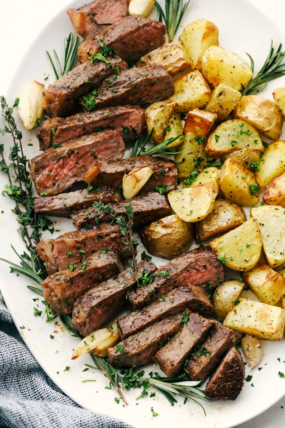 Cut up steak and potatoes on a white plate.