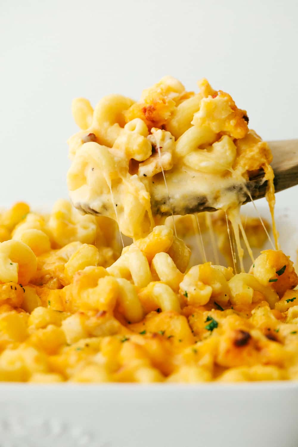 Cheesy Lobster Mac and Cheese being scooped out of a white dish.