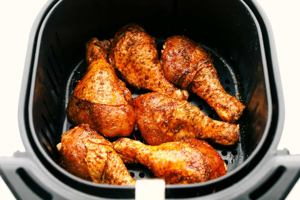 Chicken legs ready to cook in the air fryer basket.
