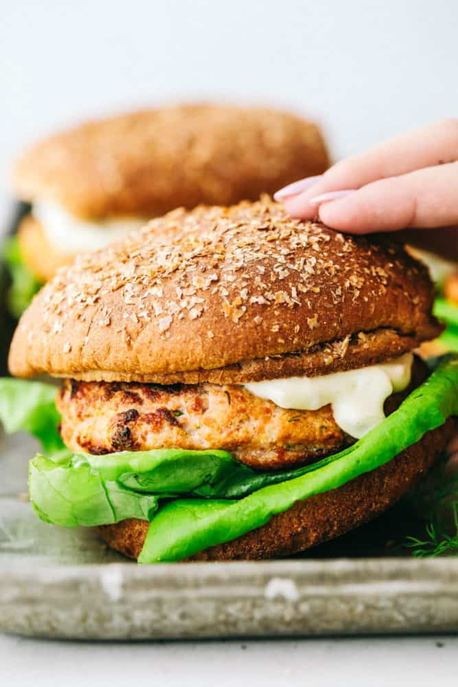 Close up on picking up a finished salmon burger.
