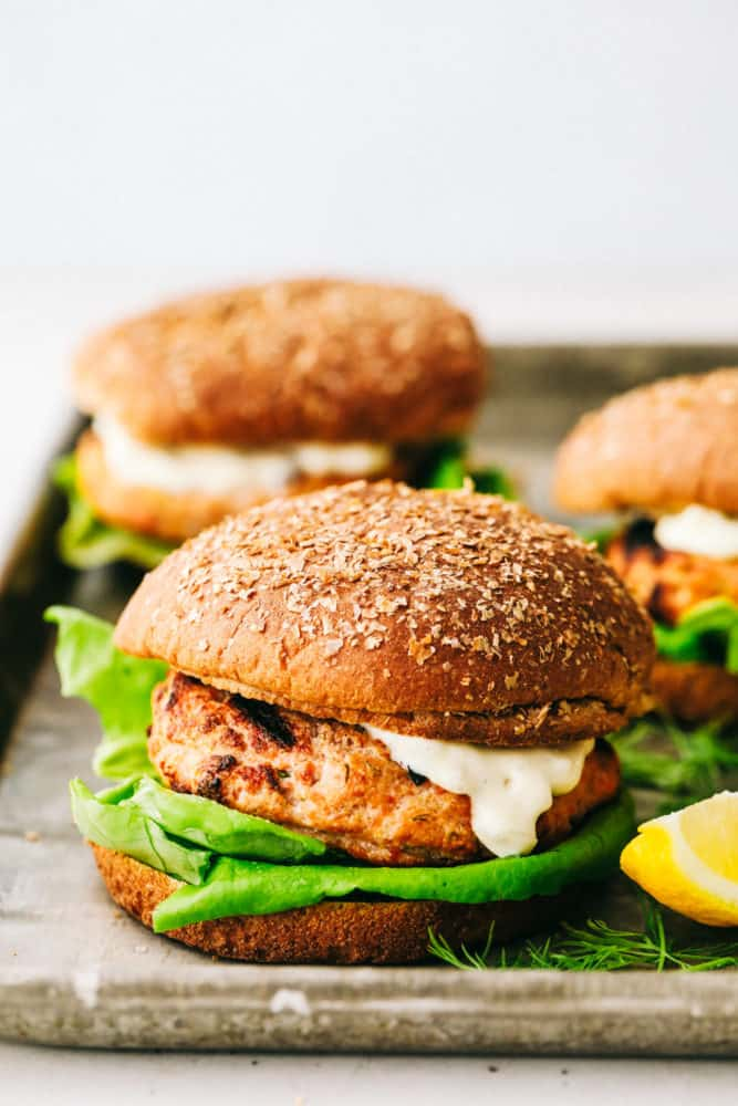 Finished salmon burgers on a tray.