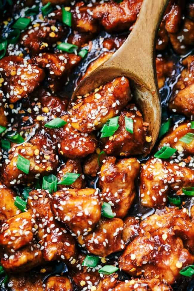 Slow Cooker General Tso's Chicken with a wooden spoon.