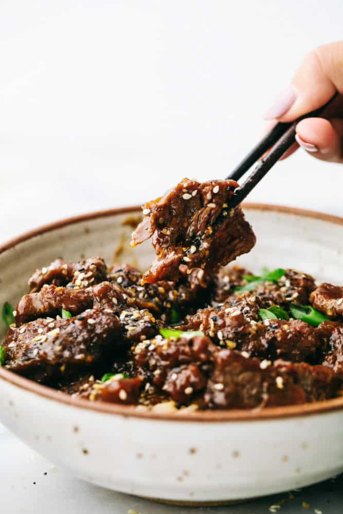 Korean beef in a bowl with black chopsticks.