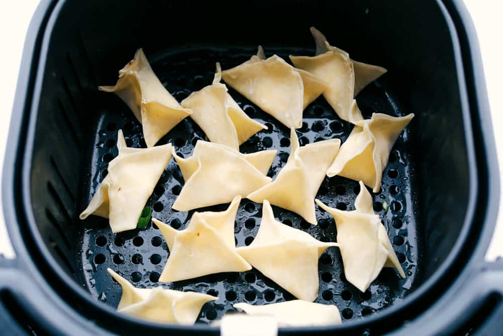 Wontons in the air fryer ready to cook.
