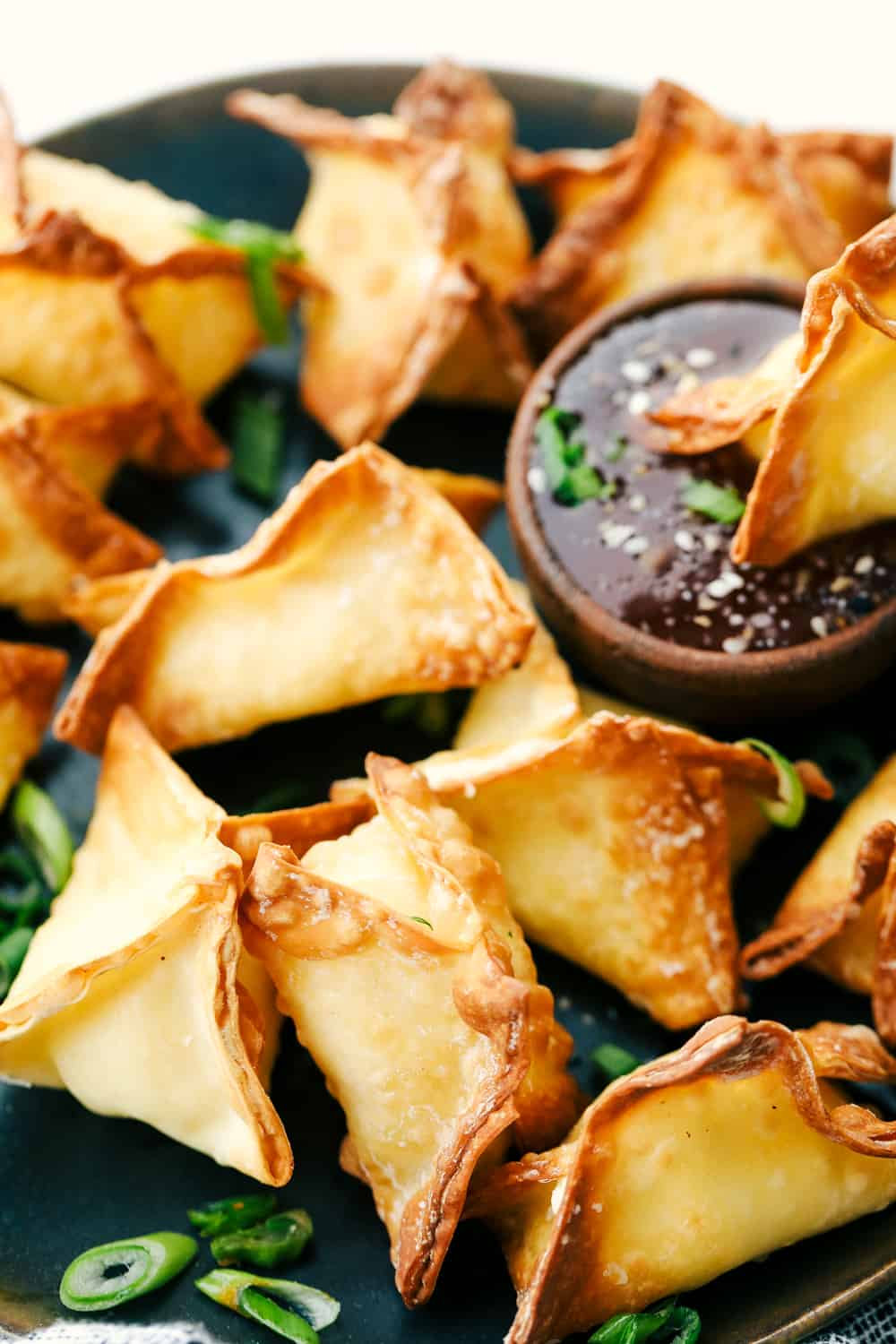 Perfectly air fried wontons on a plate with dipping sauce.