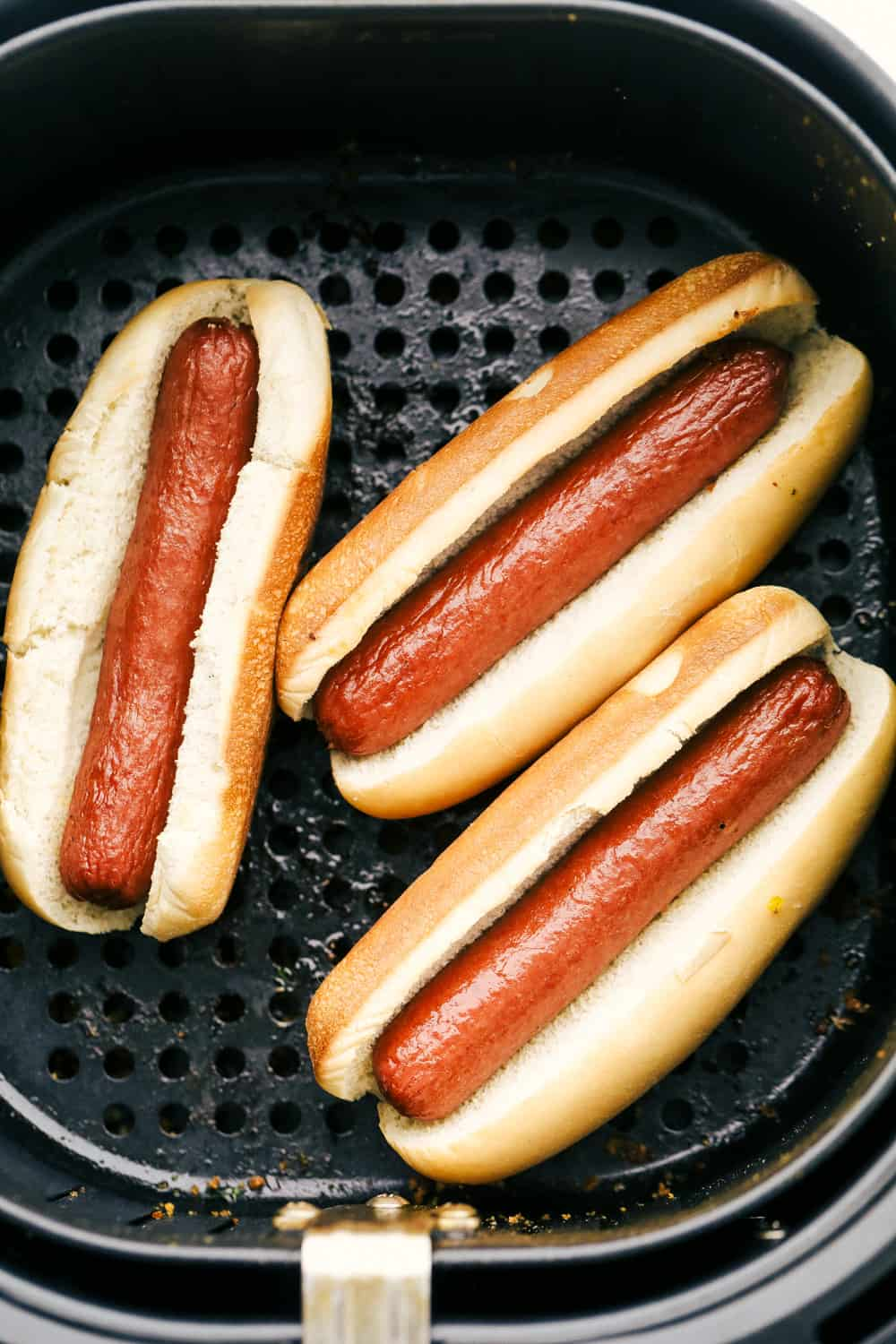 Hot dogs in buns in an air fryer.