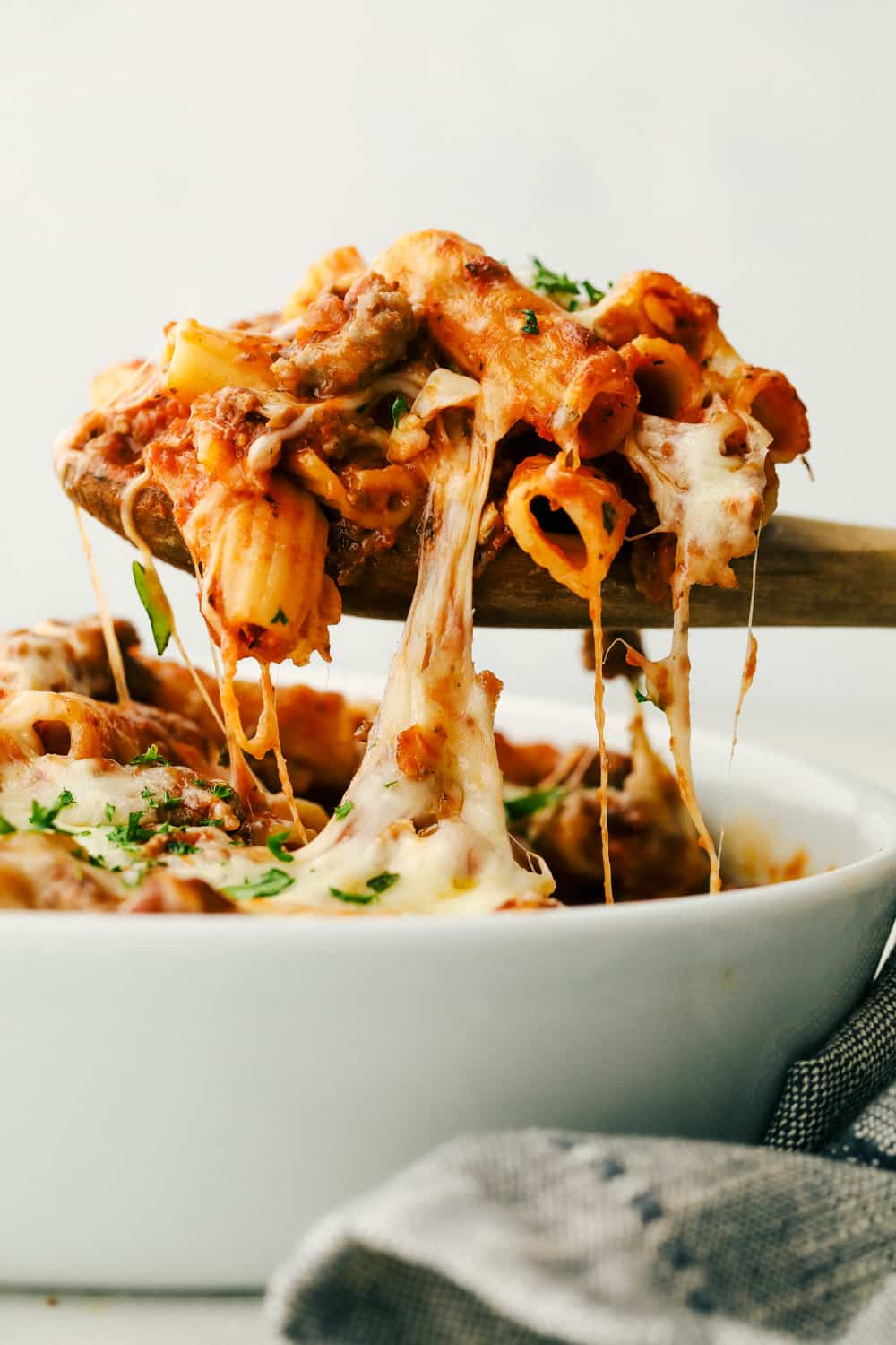 Baked rigatoni being spooned out of a bowl.