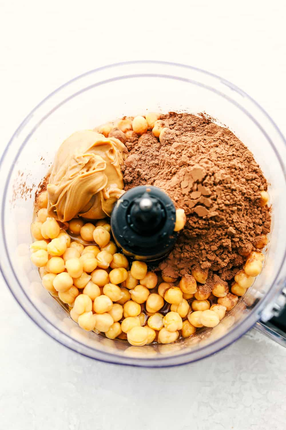 A food processor with the ingredients for chocolate hummus.