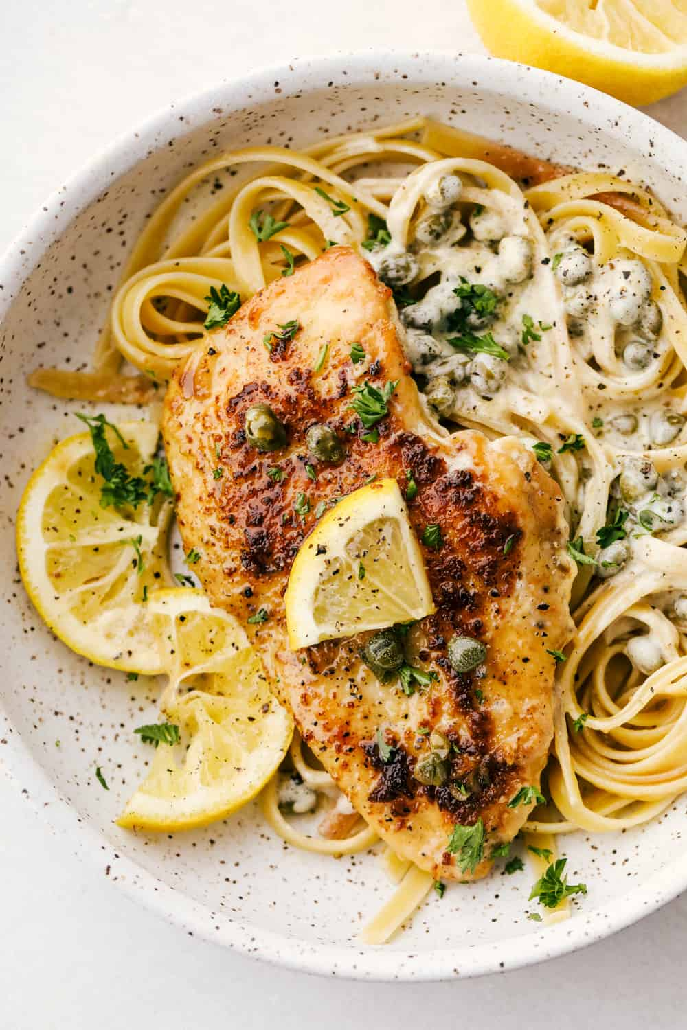 A chicken breasts with lemon piccata sauce on a bed of noodles in a bowl.