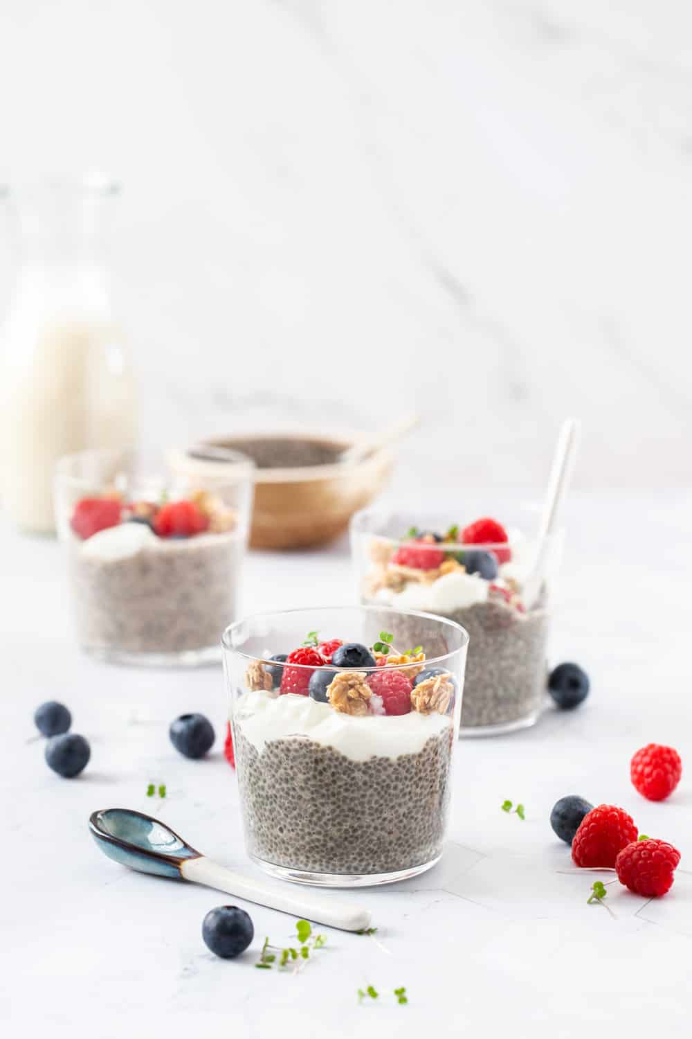 3 chia puddings in glasses topped with berries and granola.