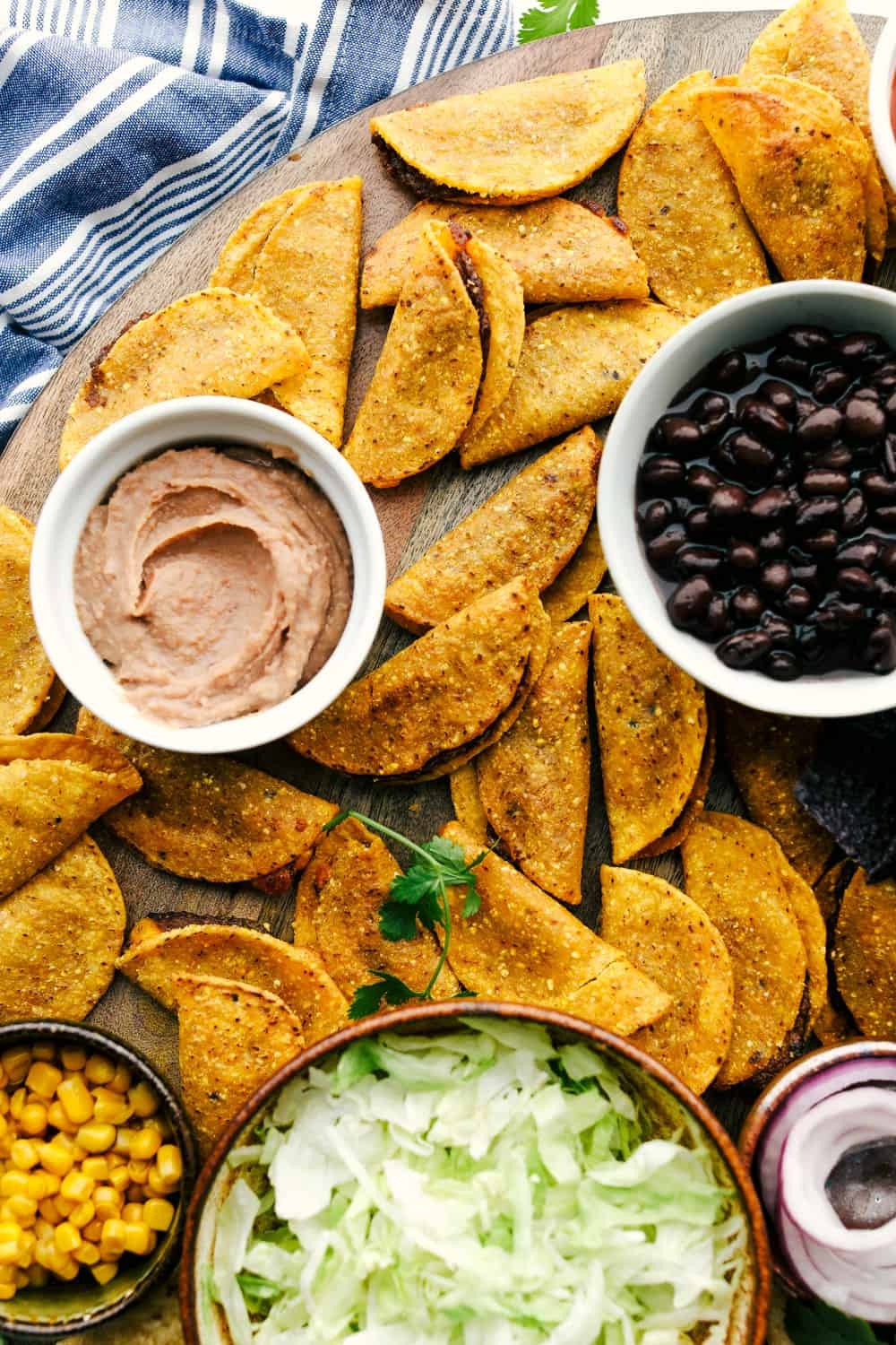 Taco board with tacos, bean dip, black beans, corn and lettuce in bowls on a board.
