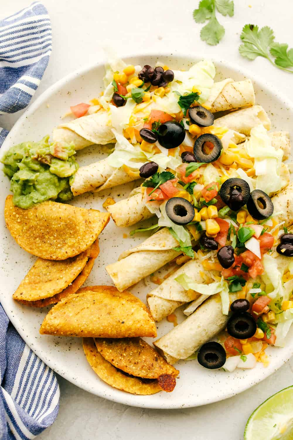 Taquitos smothered with cheese, olives, corn and tomatoes with tacos and guacamole on the side.