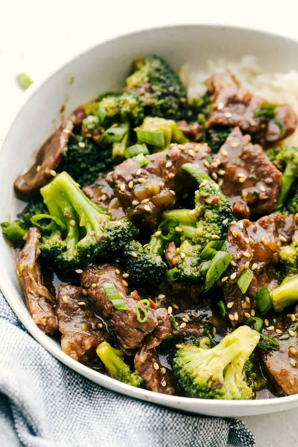 Beef and broccoli over rice in a white bowl.