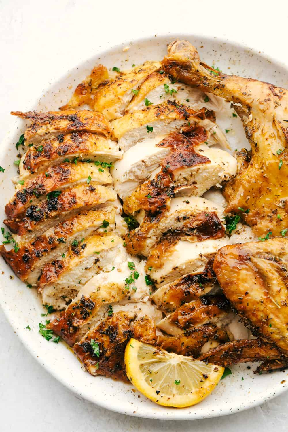 Sliced juicy chicken on a plate with a wedge of lemon.