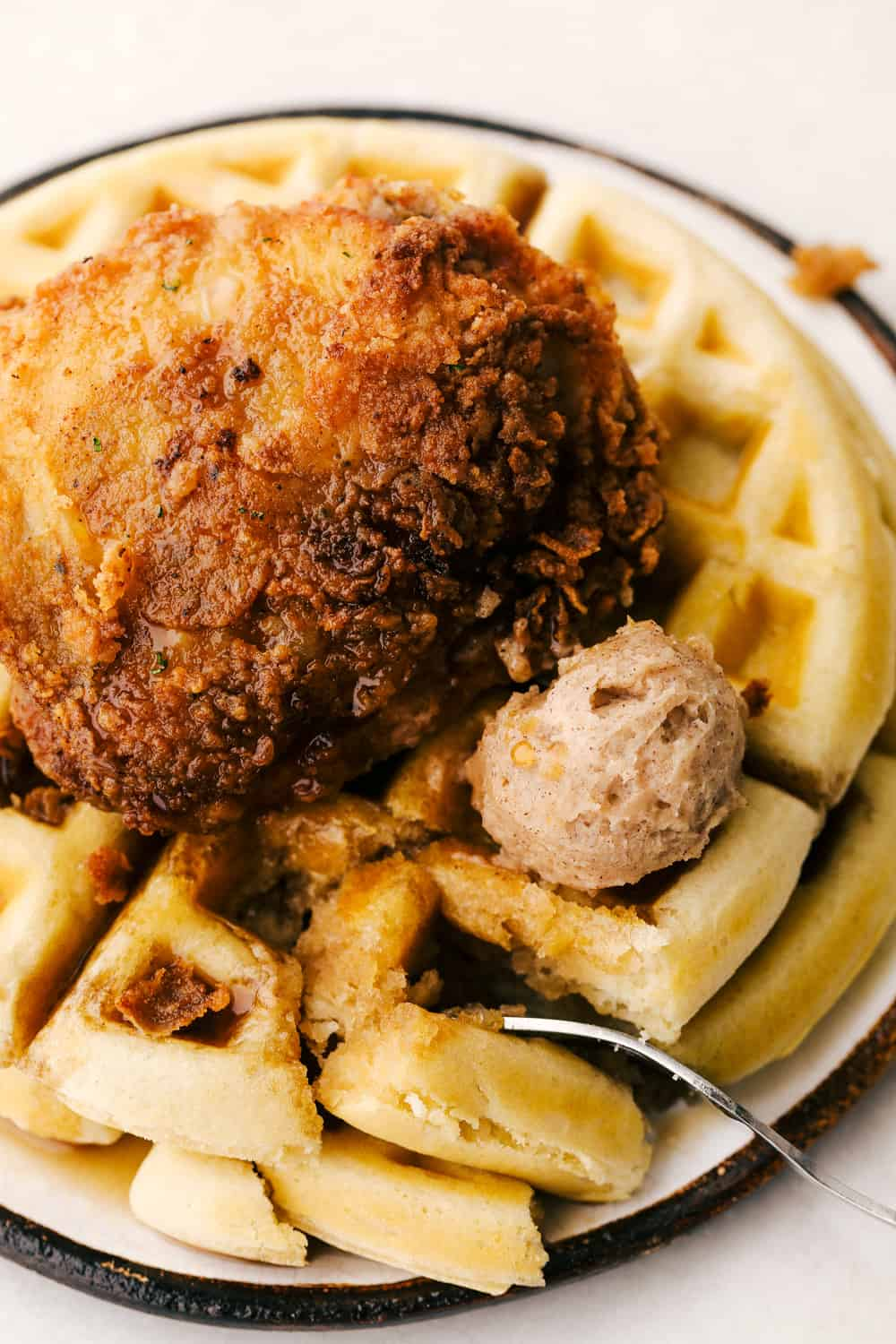 Chicken and waffles on a plate with cinnamon butter, syrup with a bite on a fork.