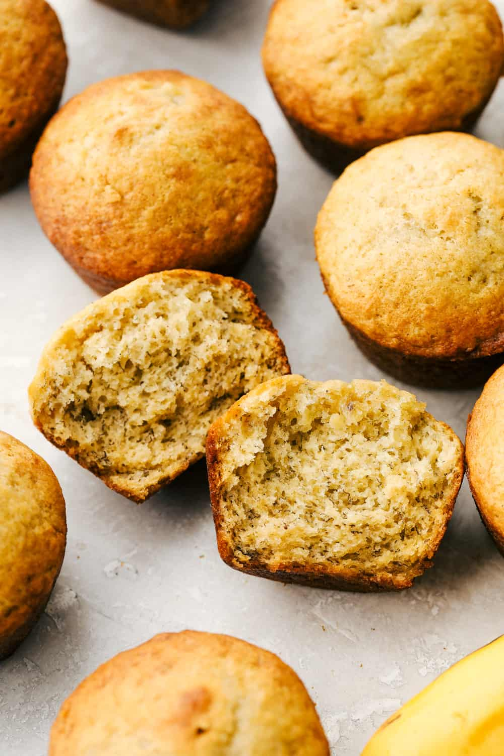 Banana muffins in a bunch with one cut open to show texture.