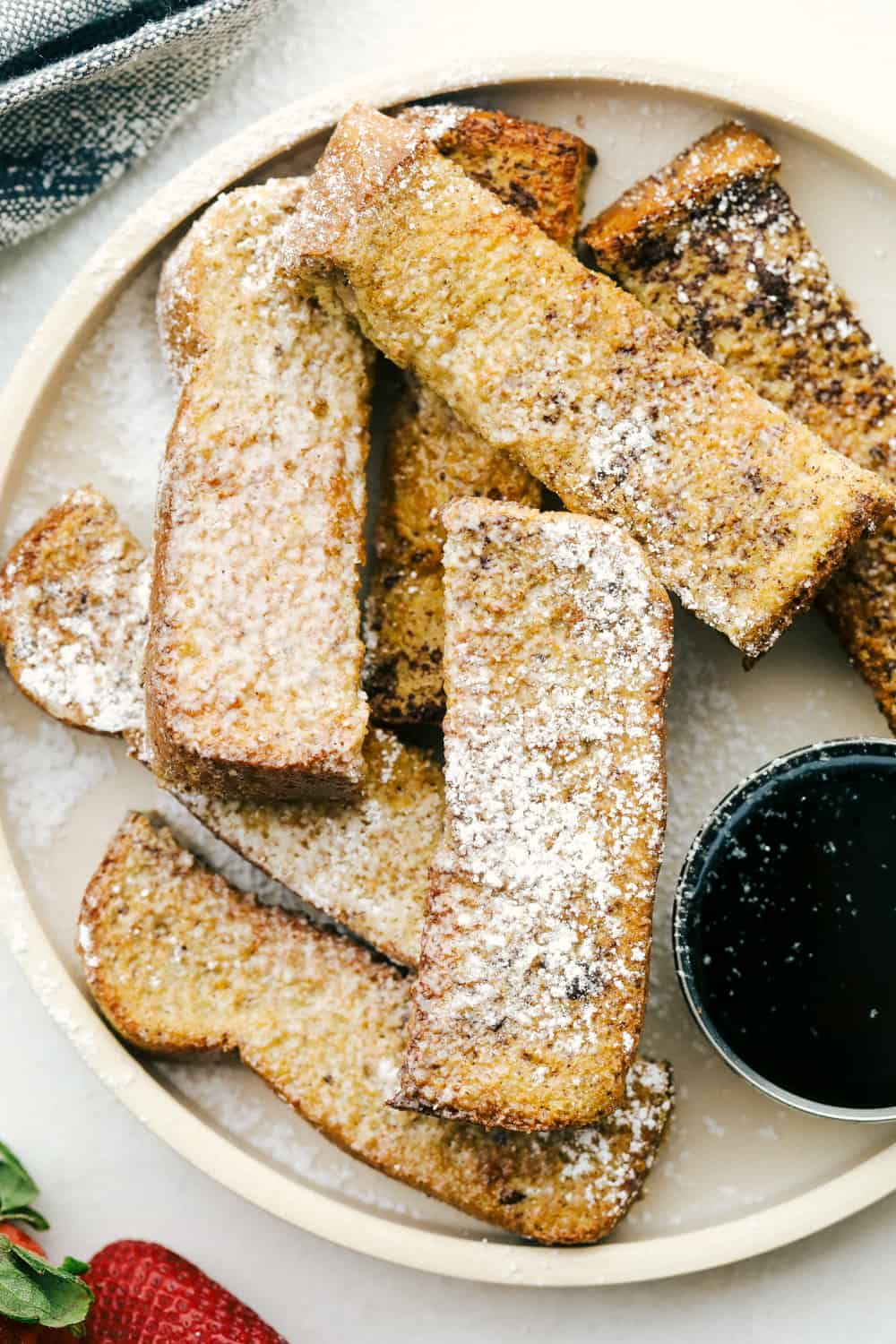 Air fryer french toast sticks layered on a plate with powdered sugar