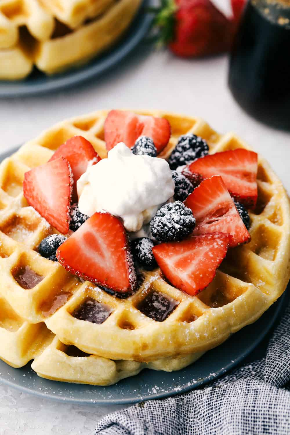 Stacked belgian waffles with berries and cream.