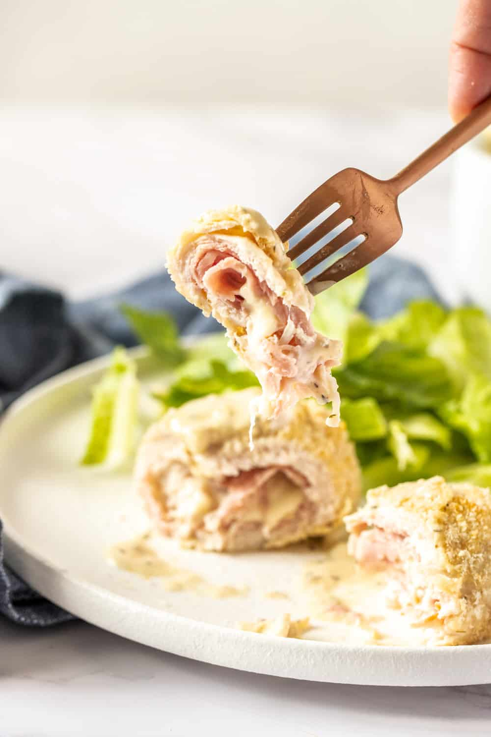 Chicken cordon bleu on a fork showing the inside layers.
