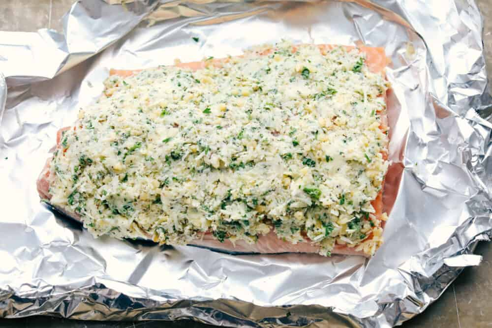 Salmon with butter, parmesan and garlic topping on top of foil.