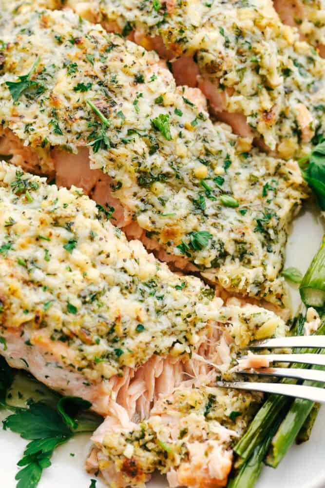 Using a fork to flake off a bite of salmon crusted with parmesan and garlic.