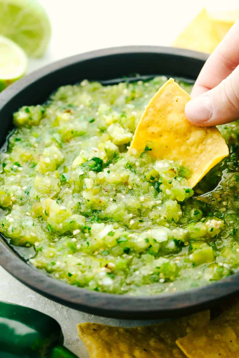 Dipping a chip in homemade salsa verde.