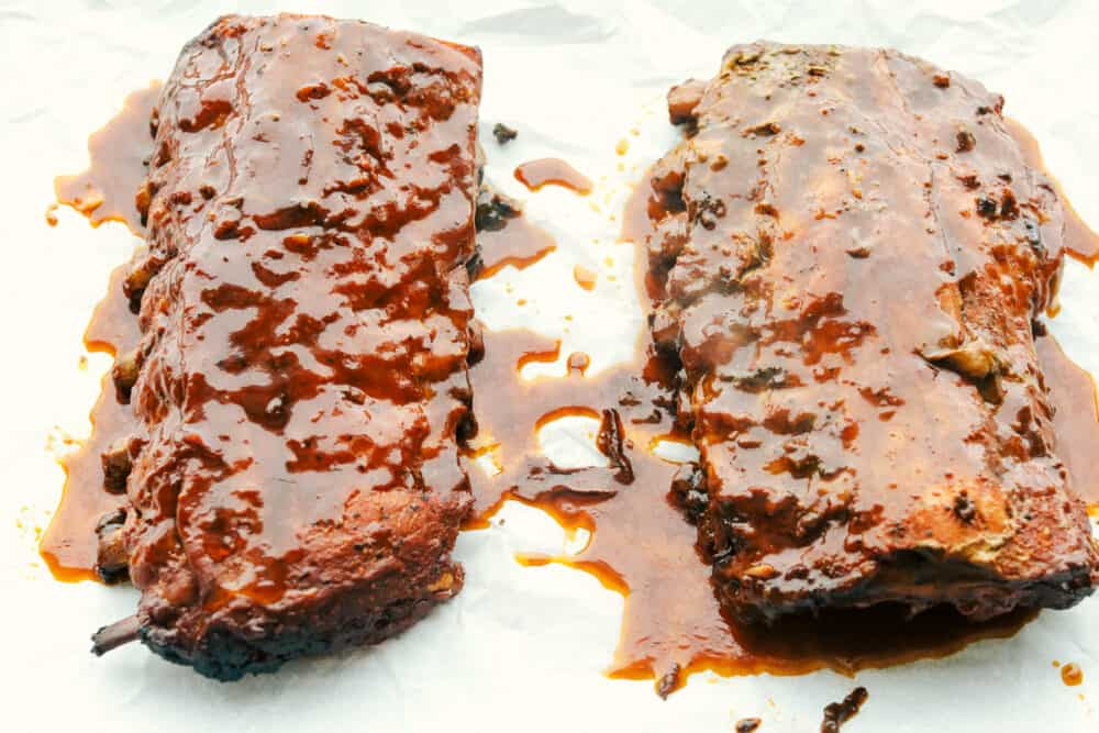 Adding extra sauce to the ribs before broiling.