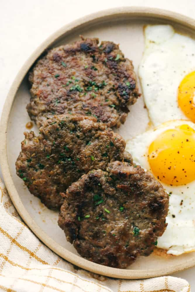 A plate of sausage with eggs on the side.