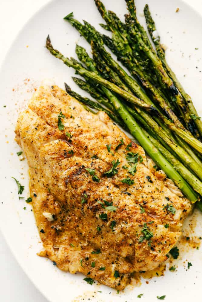 Grilled Cod on a plate with grilled asparagus.