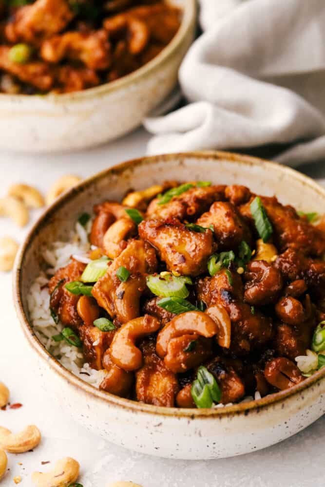 A bowl of cashew chicken on top of a bed of rice.