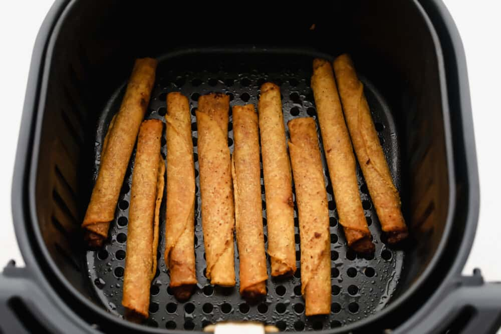 Frozen taquitos in the air fryer cooking.