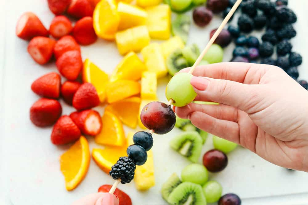 Assembling the fruit on wooden skewers.
