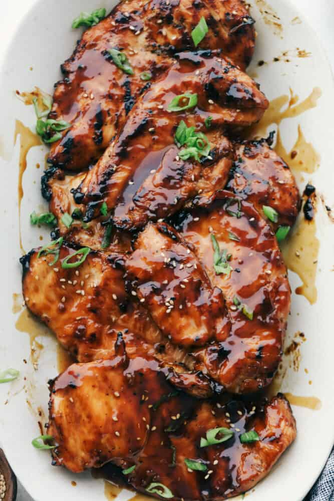 Grilled chicken with teriyaki sauce on a white plate.