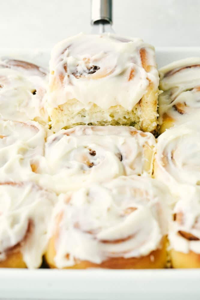 Scooping a cinnamon roll out of the pan.