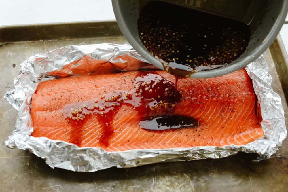 Pouring glaze over salmon in tin foil.