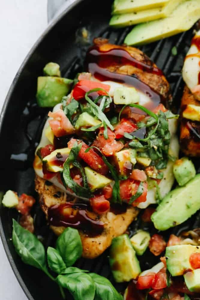 Upclose picture of chicken topped with the avocado salsa and basil.