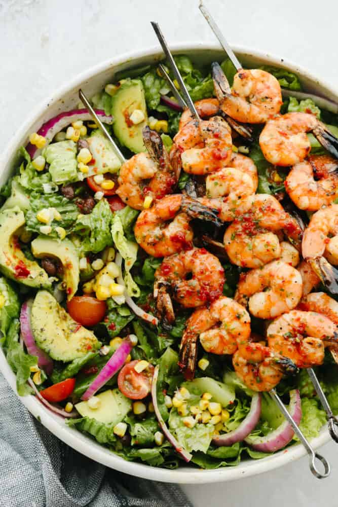 Greens in a white bowl topped with grilled shrimp.