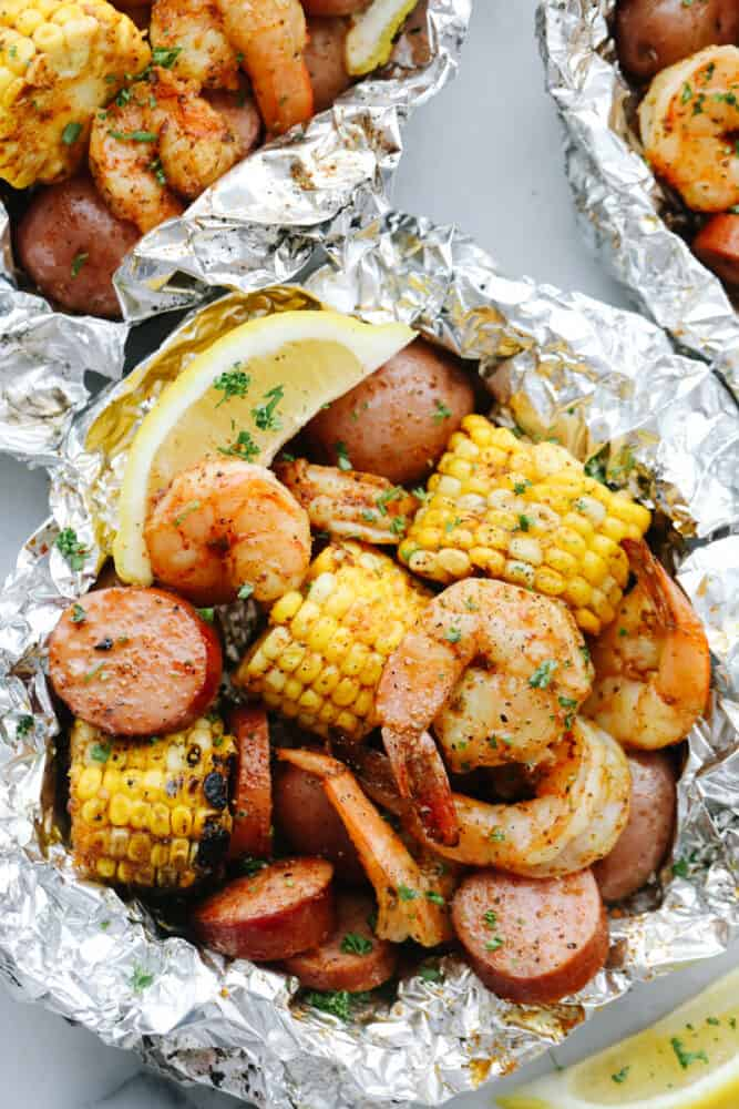Cooked shrimp, sausage, and corn in a tin foil packet.