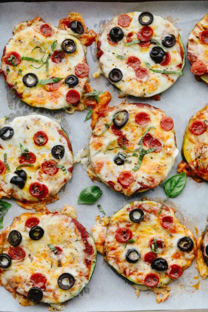 Zucchini pizza bites on a baking sheet lined with parchment paper.
