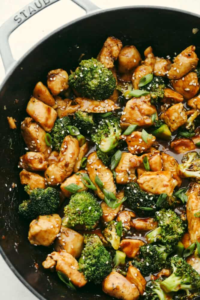 Chicken and broccoli topped with sauce in a skillet.