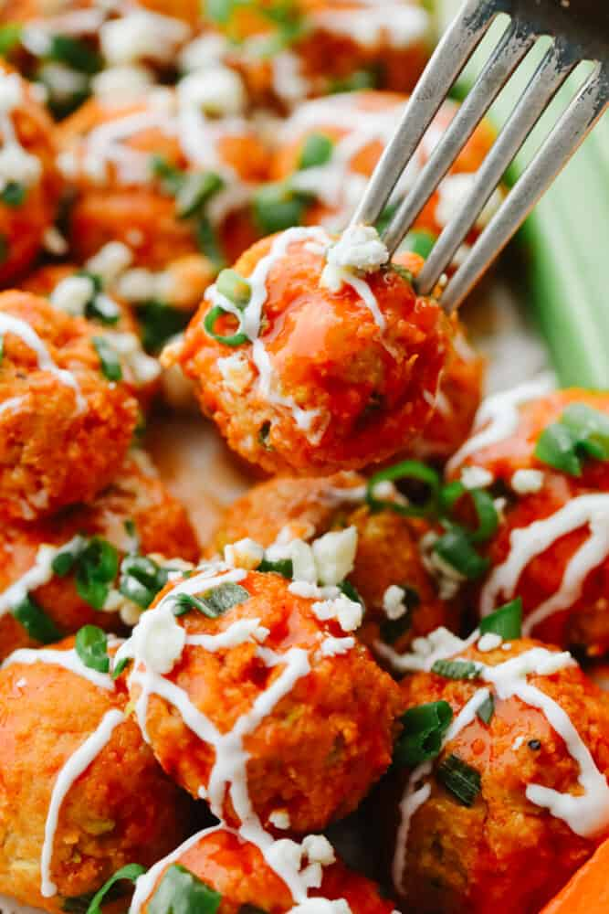 Up close photo of a chicken meatball on a fork.