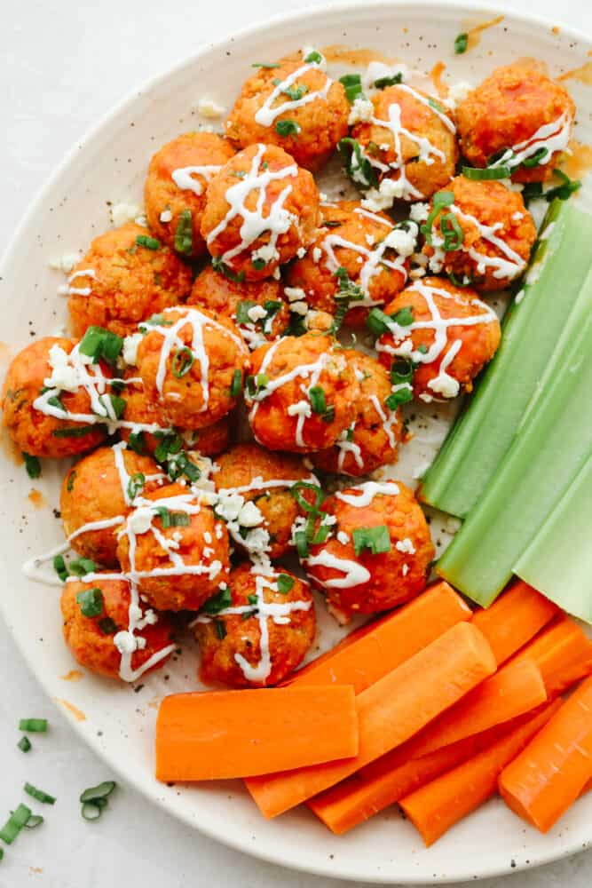 Buffalo chicken meatballs on a white plate with celery sticks.