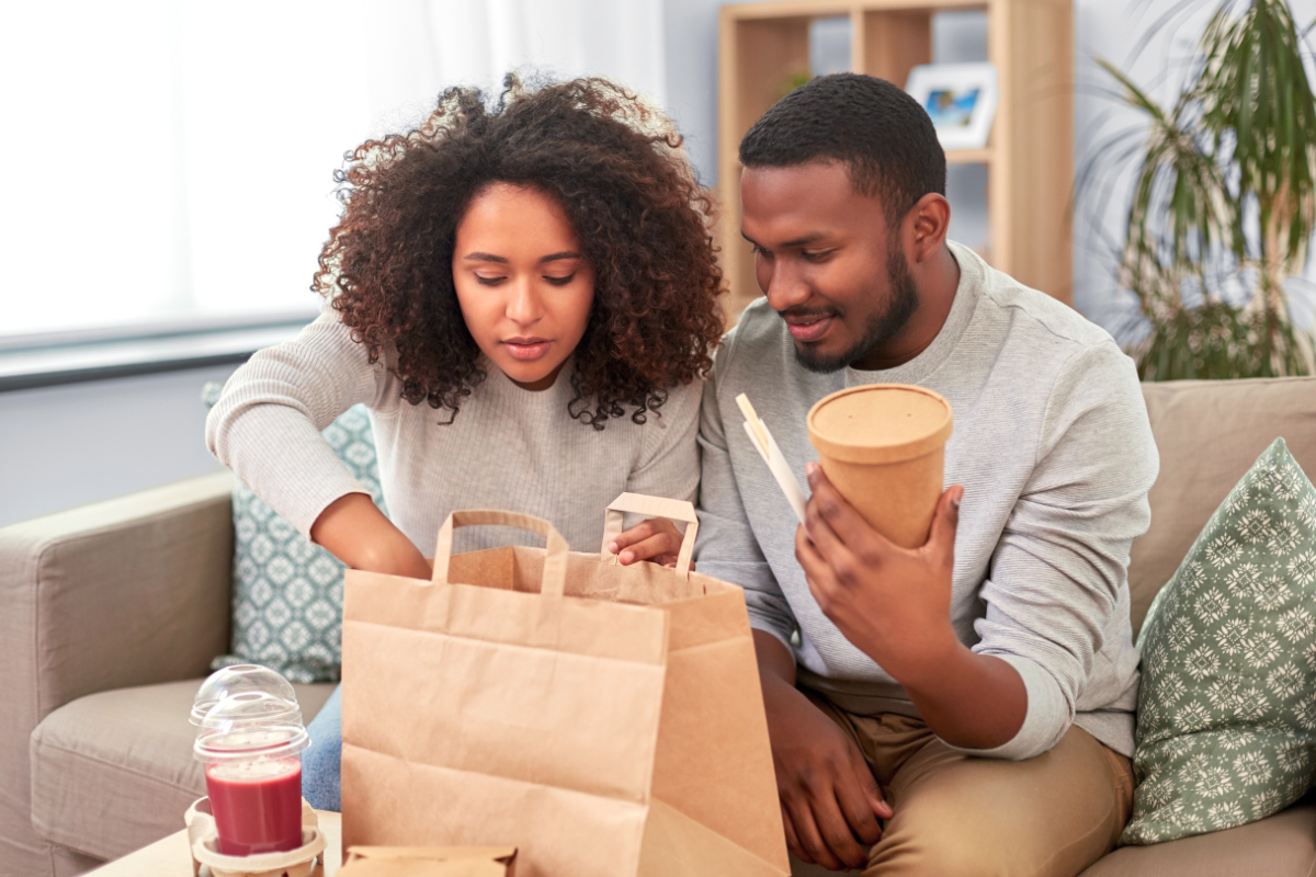 Couple eating restaurant takeout food at home